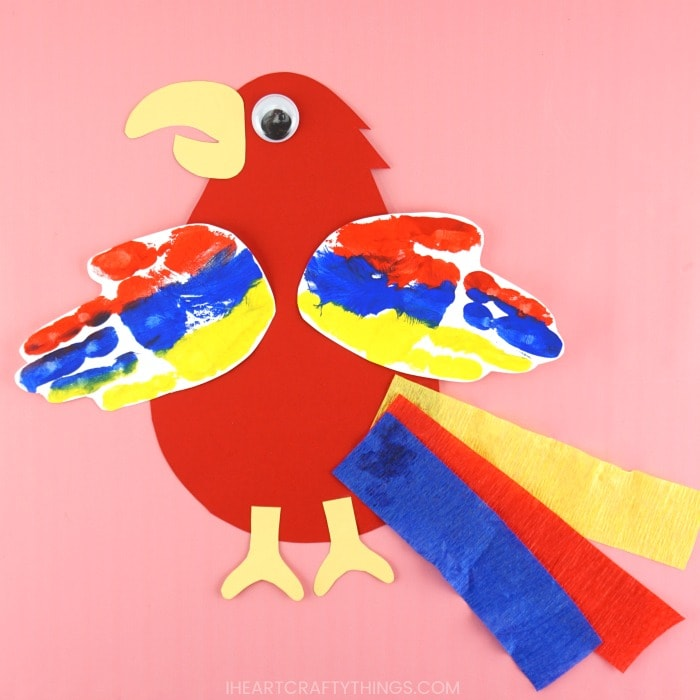 red, blue and yellow handprint parrot craft laying flat on a solid pink background.