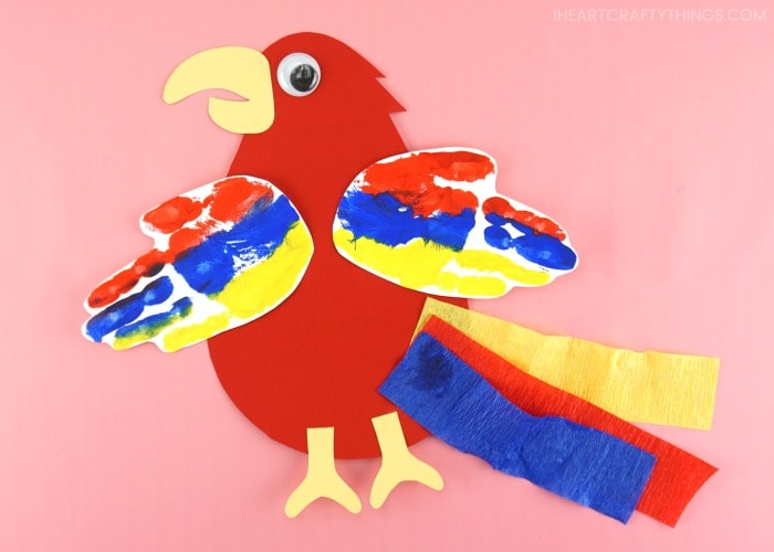 Horizontal image of finished parrot craft laying flat on pink background.