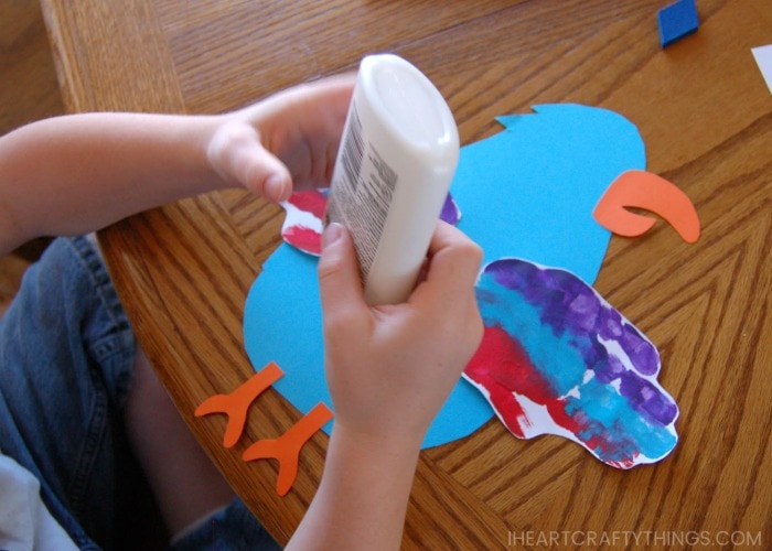 Child gluing pieces onto his parrot craft.