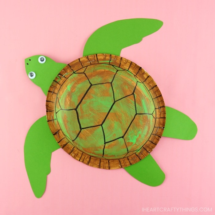 paper bowl sea turtle craft laying flat on a pink background