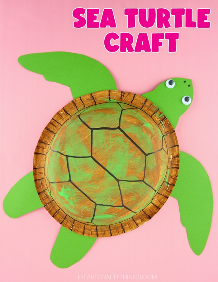 vertical image of finished sea turtle craft on pink background
