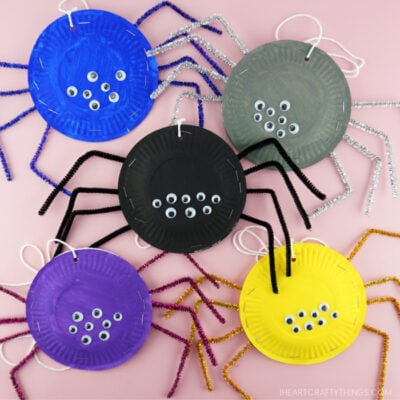 Five paper plates spiders in different colors clumped together on a pink background.