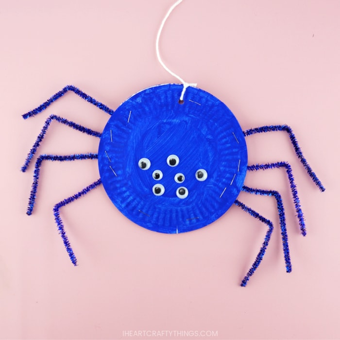 Blue paper plate spider craft laying flat on a pink background.