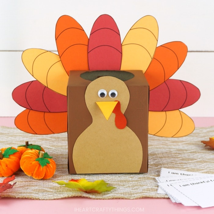 Close up square image of a tissue box made into a thankful turkey box sitting on a brown table runner with mini felt pumpkins, some fake leaves and the thankful writing note cards scattered around.