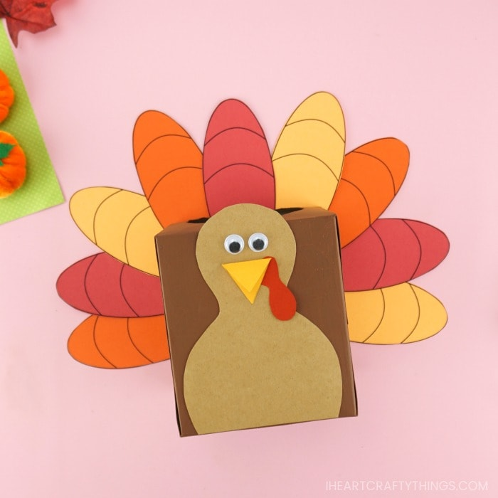 Square image of thankful turkey box laying face up on a pink background.