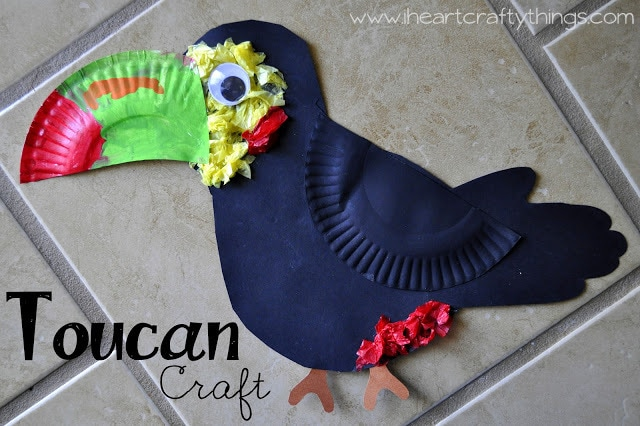 Toucan craft made by child laying on a brown tile background.