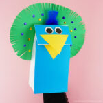 Adult hand and arm inside the paper bag peacock puppet showing how to move the beak open and closed.