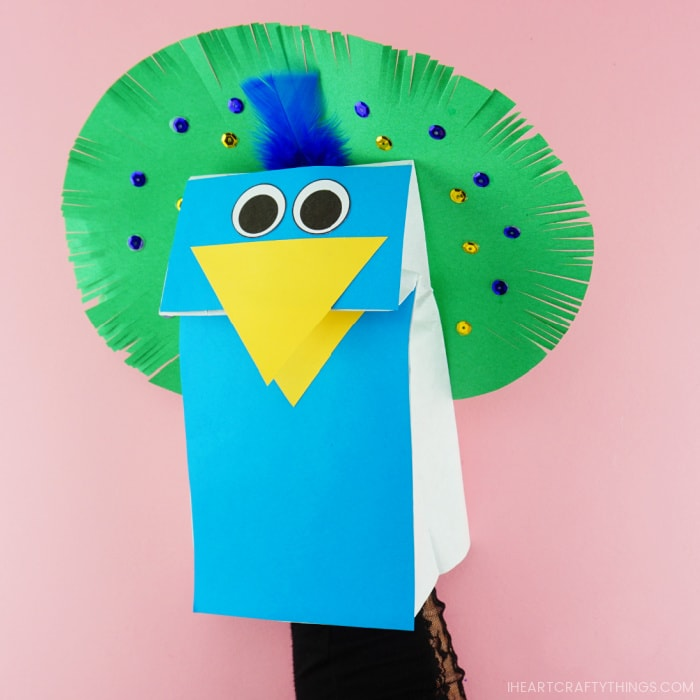 Adult hand inside the peacock puppets showing how to move the beak open and closed.