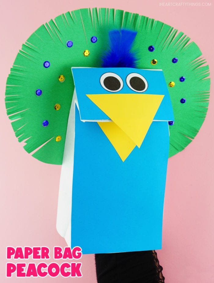 """Vertical close up image of adult with hand inside the peacock puppet, making the beak open. Words """"Paper Bag Peacock"""" in bottom left corner."""