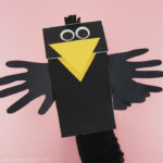 Adult with their hand inside the paper bag crow puppet showing how to make the beak open and close.