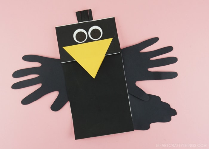 Paper bag crow puppet finished and laying flat on a pink background.