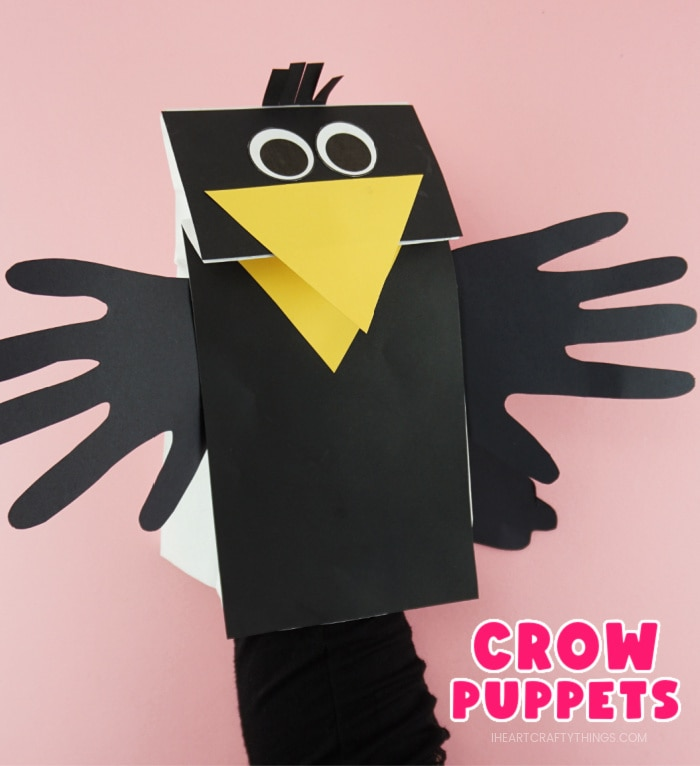 "Close up image of adult with their hand in the paper bag puppet showing how to make the crow beak open and close. The words ""Crow Puppets"" are in the bottom right corner."