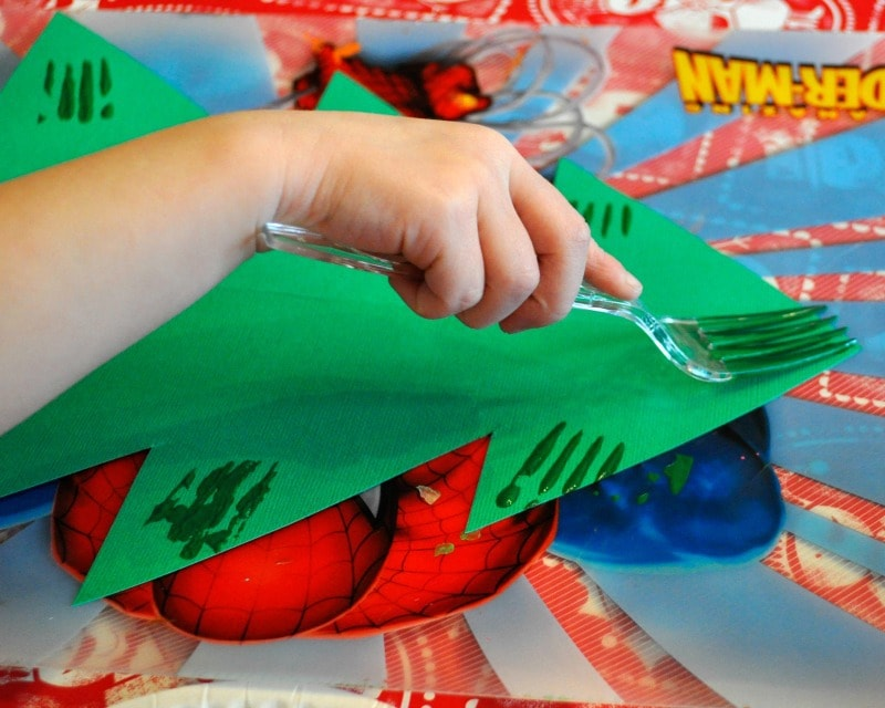 child using a fork to paint the paper Christmas tree