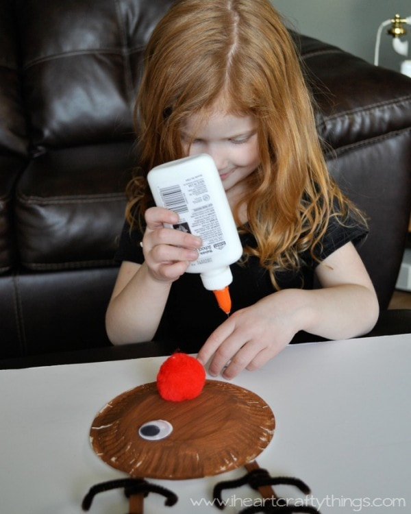 Image of child gluing the googly eyes onto her paper plate reindeer craft.
