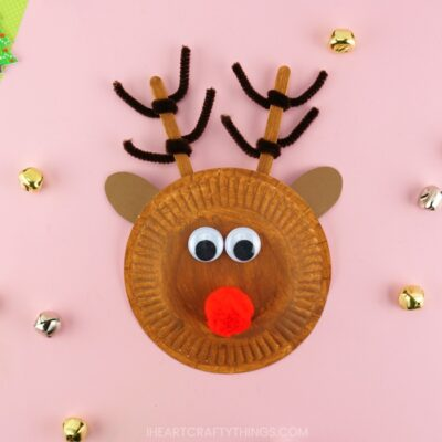 Square image of completed paper plate reindeer craft laying on a pink background with bells scattered around.