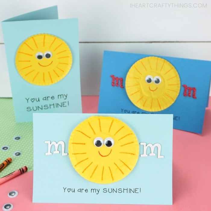 Three you are my sunshine Mother's Day cards placed on a pink table with a white shiplap background