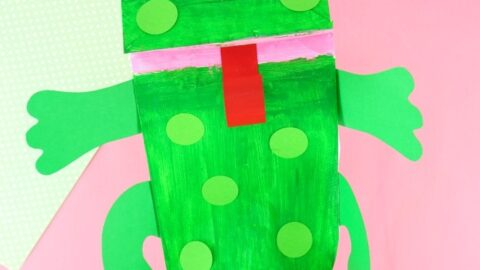 Someone with their hand inside the paper bag frog puppet on a pink background