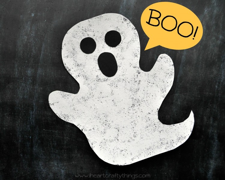 """Horizontal image of sponge painted ghost craft laying on a black chalkboard background with """"BOO!"""" written in the top right corner."""