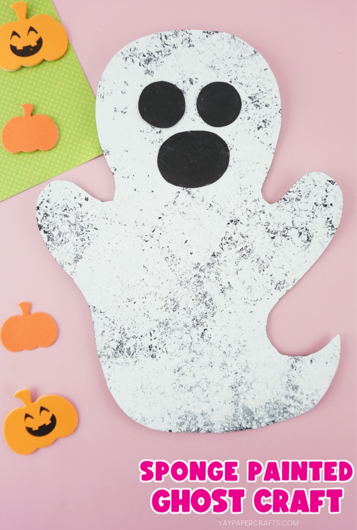 """Close up vertical image of ghost craft with pumpkin stickers scattered around it and the text """"Sponge Painted Ghost Craft"""" in the bottom right corner."""