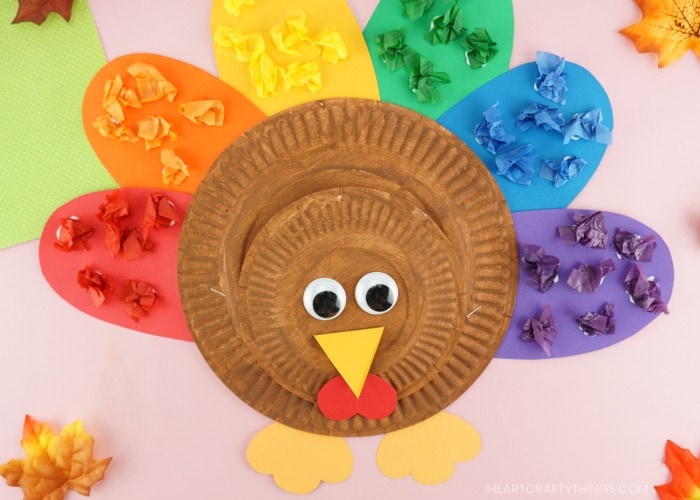 Close up image of completed rainbow paper plate turkey craft laying on a pink background.