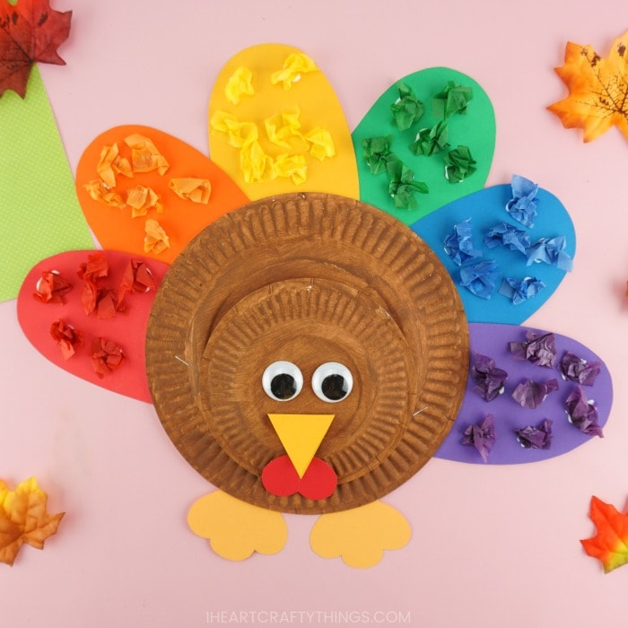 Square close up image of rainbow turkey craft laying on a pink background with fall colored leaves scattered around the turkey.