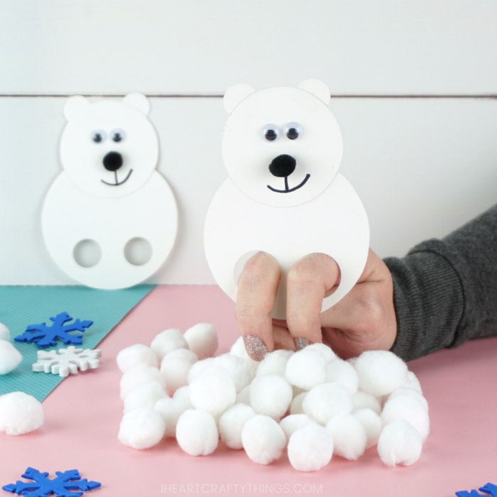 Adult with their fingers inside the polar bear puppet playing with it and using it to knock down a pile of white pom poms.