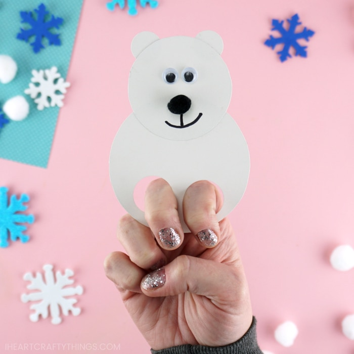Close up image of adult with their fingers inside the polar bear finger puppet showing how to use it.
