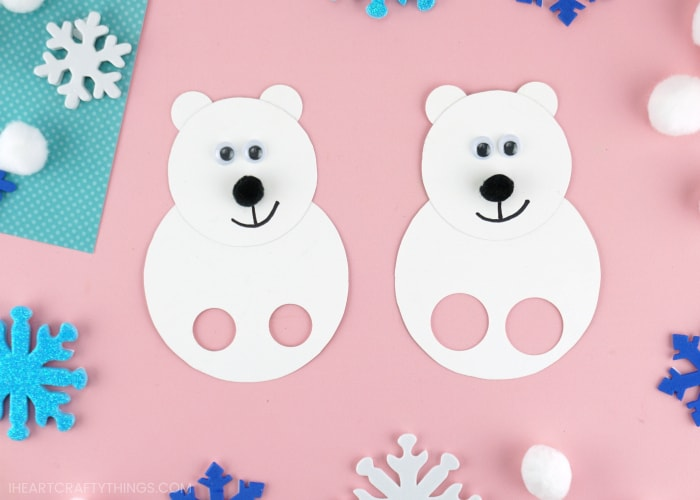 Two polar bear finger puppets laying next to each other on a pink background with snowflake stickers scattered around.