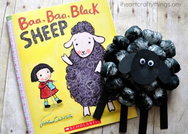 Finished black sheep craft laying next to Baa, Baa Black Sheep book.