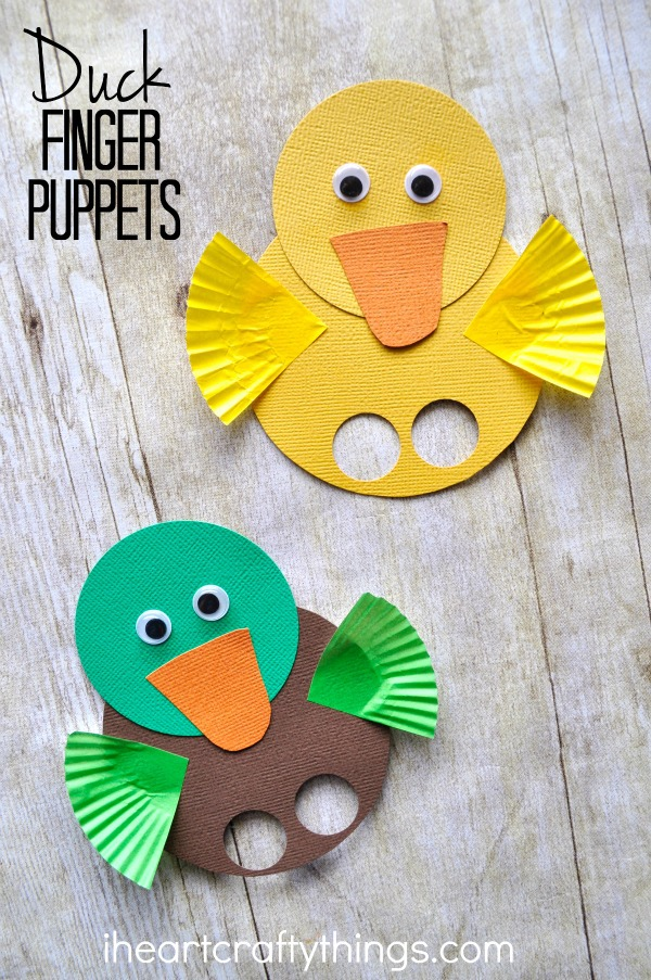 """Vertical image of a yellow duck finger puppet and a mallard duck finger puppet laying on a faux wood background with the words """"Duck Finger Puppets"""" in the top left corner."""