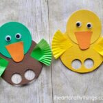 Yellow duck finger puppet with green and brown duck finger puppet laying next to each other on a faux wood background.