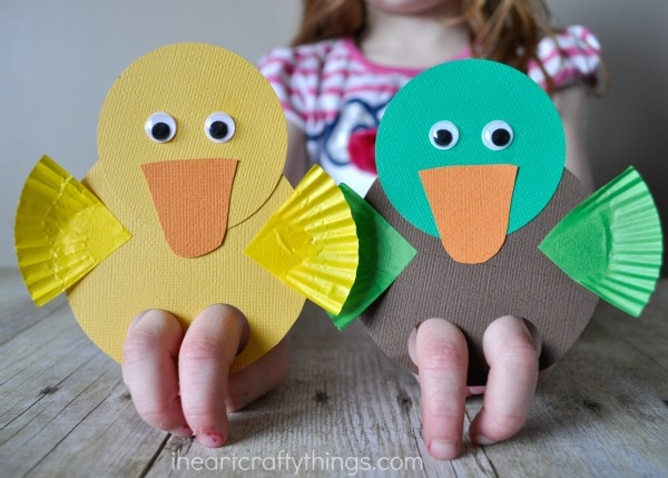 Child playing with a yellow duck and mallard duck finger puppets.