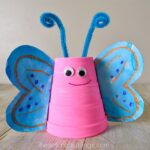 Close up image of pink foam cup butterfly craft with blue wings and blue antennae.