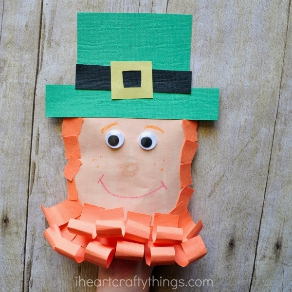 Close up image of child with their hand inside the leprechaun envelope puppet