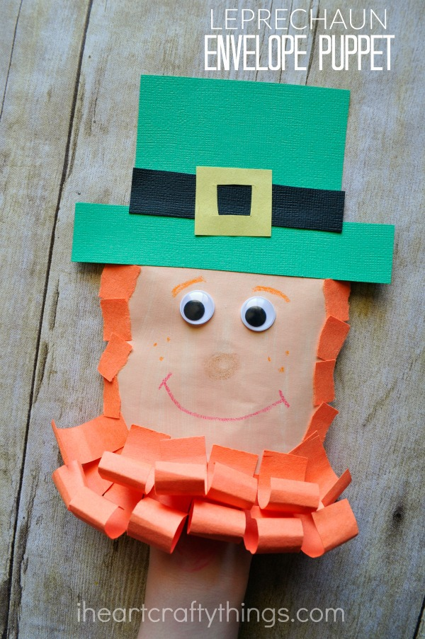 """Vertical image of child playing with the leprechaun craft puppet with the words """"Leprechaun Envelope Puppet"""" in the top right corner."""