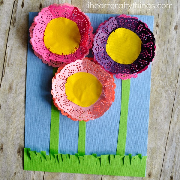 Square image of flowers craft made out of paper doilies and colored paper.