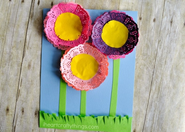 Finished paper doily flowers craft laying on a faux wood background.