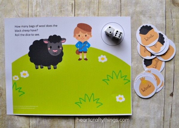 Preschool counting game printable laying with dice in the circle on the printable and the bags of wool cut out and placed next to the printable.