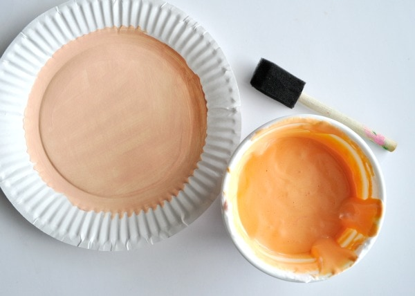 White paper plate with the center circle painted with peach paint sitting next to a bowl of mixed orange puffy paint and a paintbrush ready to paint the paper plate with.