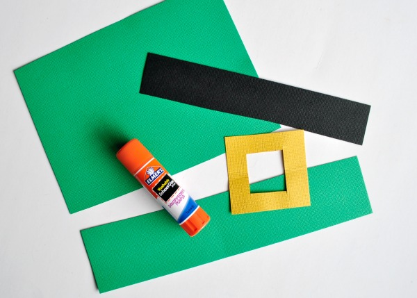 Leprechaun hat pieces cut out of green black and yellow cardstock paper with a Elmer's glue stick sitting on top of them.