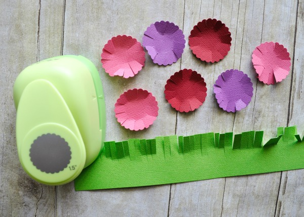 pink, purple and red scallop circles cup out laying next to a scallop circle punch and a rectangle of green cardstock paper that has slits cut along one end to look like blades of grass.