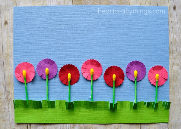 Completed q-tip flowers craft laying flat on a faux wood background.