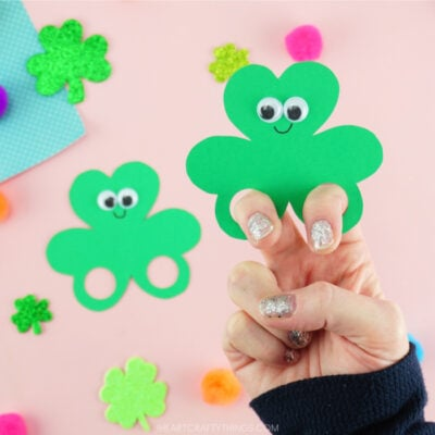 Image of one close up in focus shamrock finger puppet with adults fingers in the holes and one out of focus shamrock puppet laying next to it.