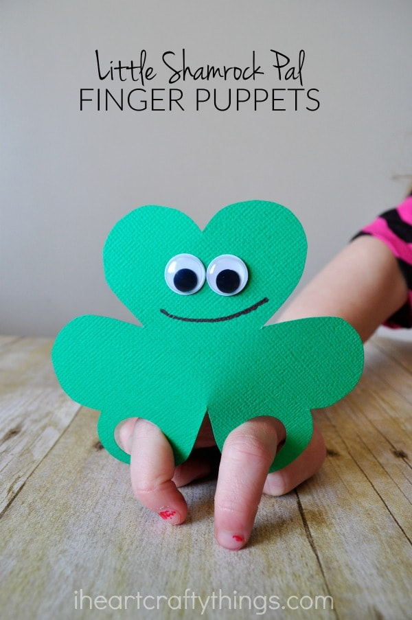 """Vertical close up image of child playing with a shamrock finger puppet with the words """"Little Shamrock Pal Finger Puppets"""" in the top center."""