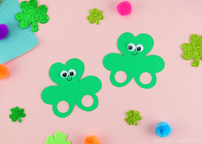 Two shamrock finger puppets laying side by side on a pink background with glittery shamrock stickers and colored poms scattered around them.