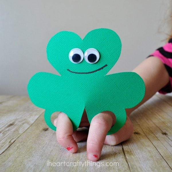 Close up image of child playing with the finished shamrock finger puppet.