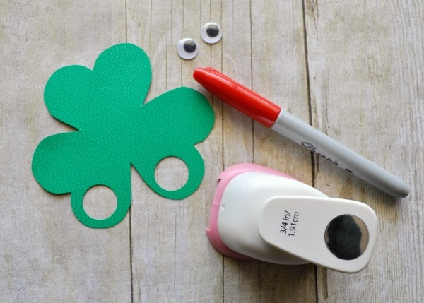 circle punch, red marker and googly eyes laid on faux wood background with a shamrock finger puppet shape