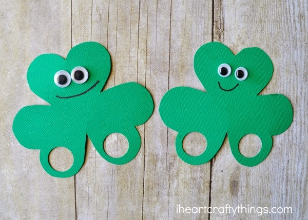 Two finished shamrock finger puppets laying side by side next to eacher.