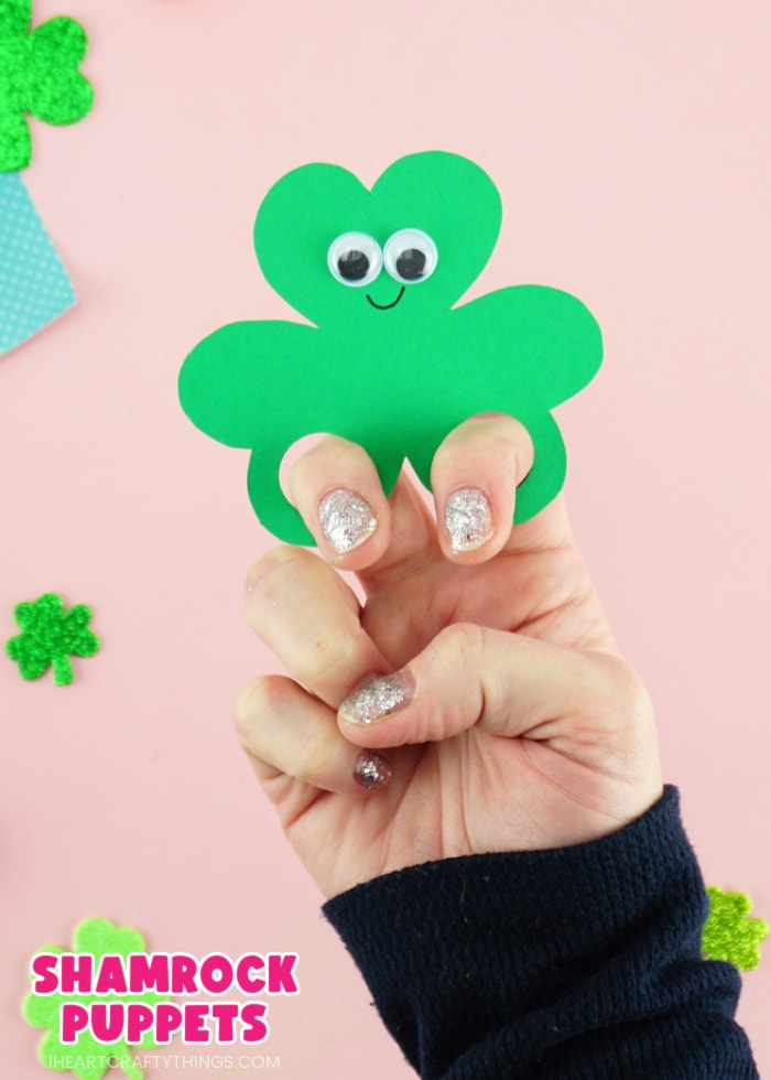 """Vertical close up image of someone with their fingers in the shamrock finger puppet with the text """"shamrock puppets"""" in the lower left corner."""