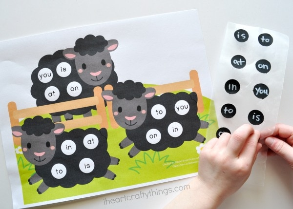 Child peeling a sight word sticker off the page and placing it on the sight words printable.
